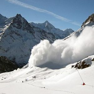 Avalanche on snowy slope with mountains in the background