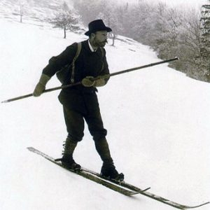 Man skiing downhill on wooden skis with single large ski pole