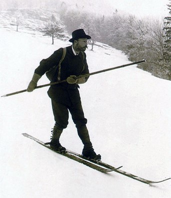 Man skiing downhill with single pole, circa 1905