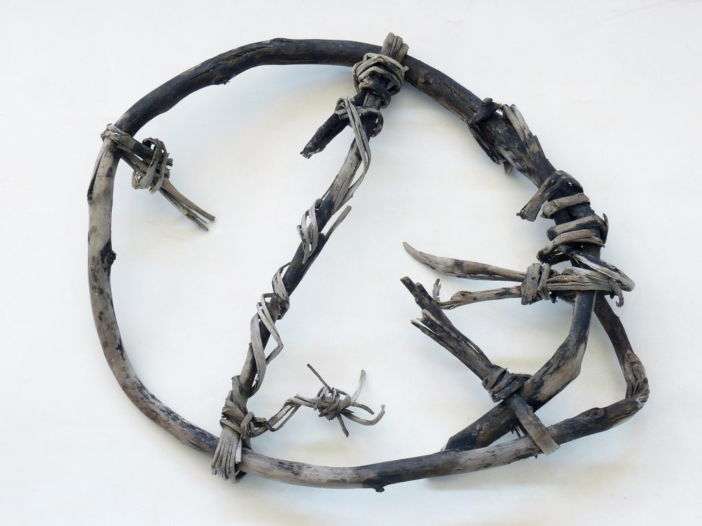 Ancient snowshoe made of branch bent into a circle with cross-piece