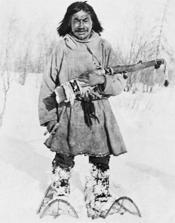 Man on large snowshoes carrying beaded gun case