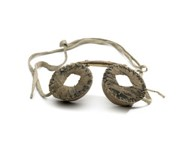 Snow goggles made of two round pieces sewn of birch bark with holes in the middle, connected by birch bark (?) strip