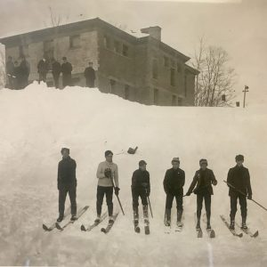 6 boys on skiis in front of small snow hill with school building in the background
