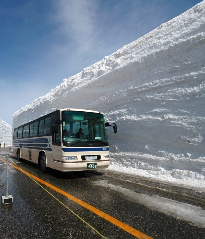 Bus on road with towering walls of snow (about twice as high as the bus)