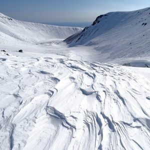 Directional snow drifts hardpacked from wind near mountains