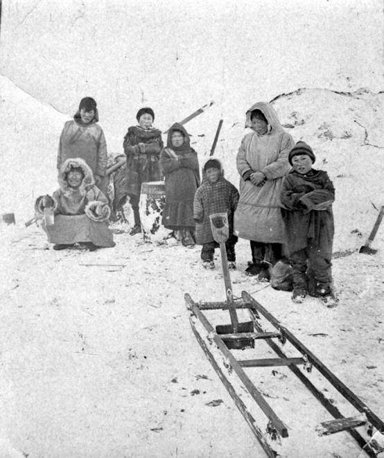 A family poses in the snow with a wooden sled frame and snow shovel in the foreground