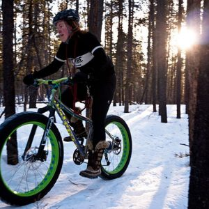 person riding fat-tire bike on snow through forest