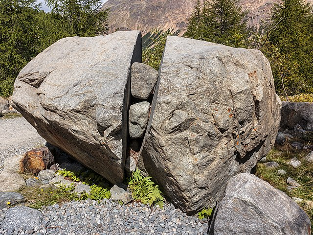 large boulder split down the middle with smaller rocks stuck inside the crack