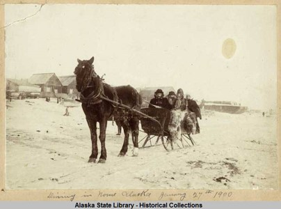 four people wrapped in furs in a horse-drawn sleigh