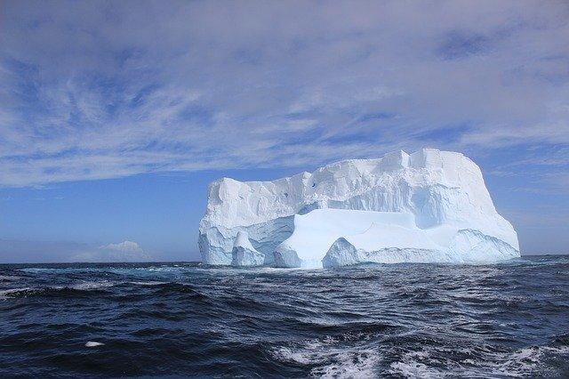 Large white iceberg floating on dark blue water