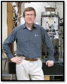 A man standing in front of a large piece of lab equipment