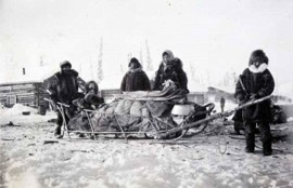 Athabascan family dressed in furs standing near a sled containing furs, snowshoes, and a child