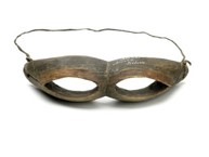 Carved from one piece, shaped wooden snow goggles with two oblong eye holes cut