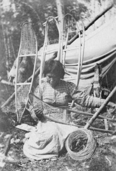 A woman kneeling on the ground making snowshoes