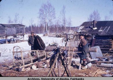 Dene (Athabascan) man and boy outside of cabin with wooden sled and snowshoes