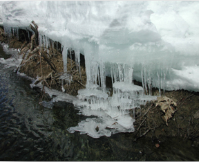 Snow, icicle formations, and creek