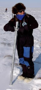 Person in snow with long metal tube for taking snow core samples