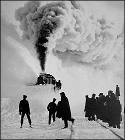 Train in deep snow spewing snow into the air with a rotary plow