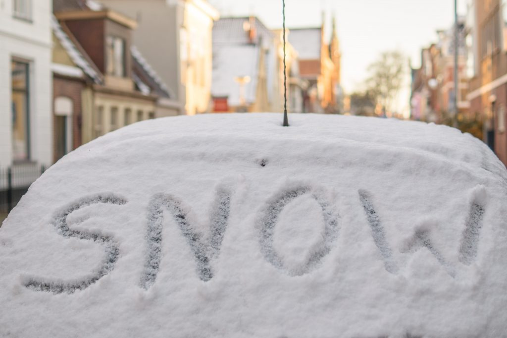 SNOW written on snow-covered car windshield