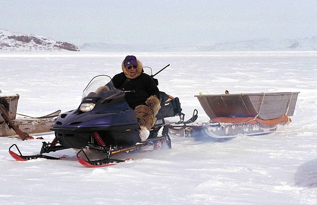 Man on a snowmobile towing a sled on the snow-covered ice