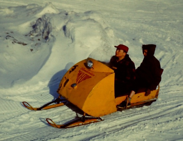 Two people riding a small yellow snowmobile