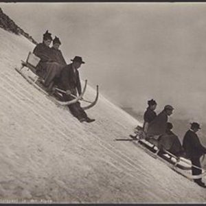 Adults on toboggans sledding downhill on a snowy slope