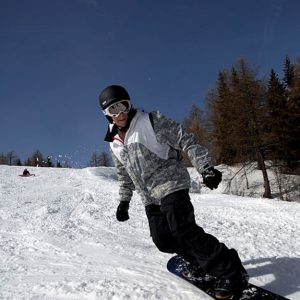 Man on snowboard on snow-covered slope