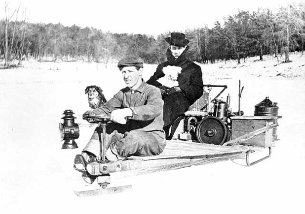 A man and a woman driving a prototype motorized snow vehicle