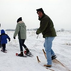 3 adults and one child on modern and traditional wooden snowshoes walking on snow