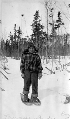 Tanana boy wearing snowshoes standing on a snow-covered path in the forest