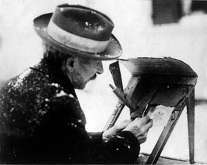 Man in hat with small image of snowflake and old fashioned photograph equipment, black and white
