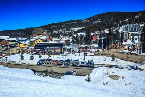 Ski resort - buildings and parking lots in front of ski slopes under blue sky
