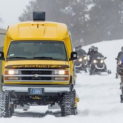 a yellow tracked vehicle with sightseers and a line of snowmobilers on a snow-covered road