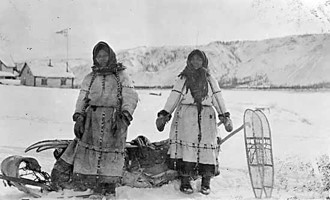 Two indigenous women dressed warmly with a loaded toboggan sled