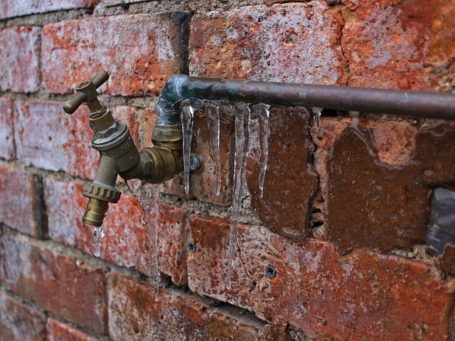 Water pipe and spigot against brick wall with icicles hanging from pipe