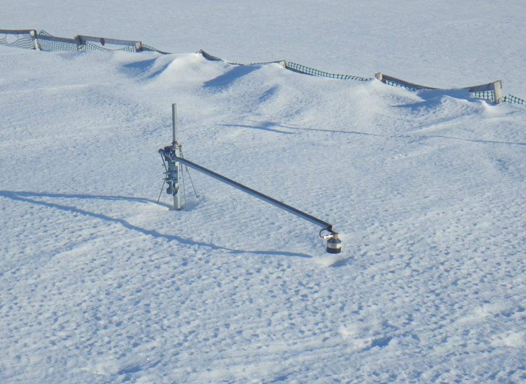 Fence with snowdrift and scientific instrument in foreground
