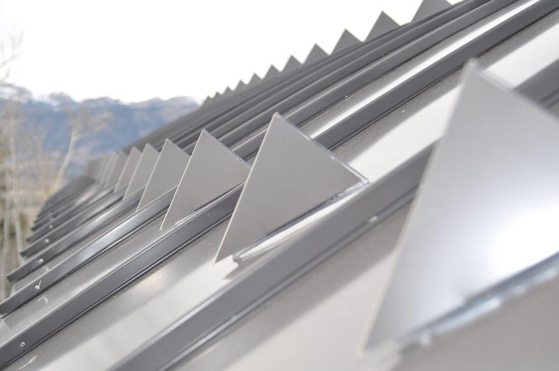 Triangular metal snow guards on metal roof