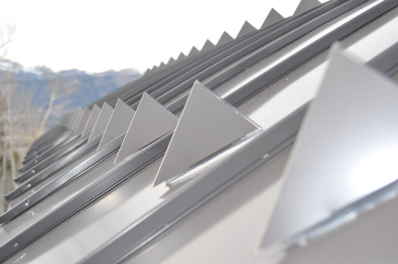 Triangular metal snow guards on metal roof