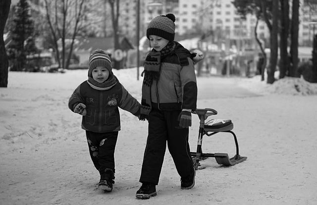 Two kids with sled-bike in a snowy park (black and white image)